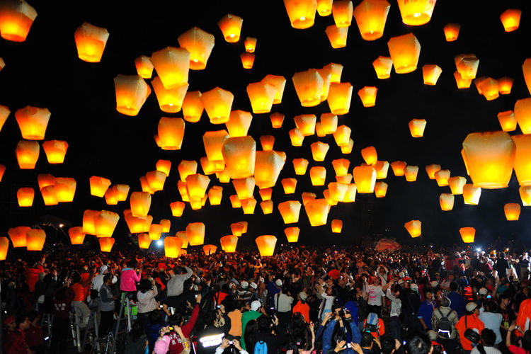 Large crowd looking at illuminated lanterns against sky at night