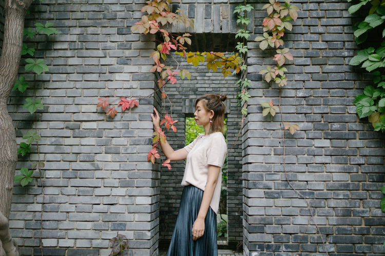 Full Length Of Beautiful Woman Standing Against Brick Wall
