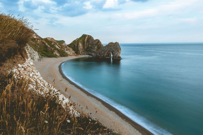 Durdle Door, Dorset Durdle Door, Dorset Durdle Door EyeEm Selects Water Sea Scenics - Nature Sky Beauty In Nature Land Outdoors Horizon Tree Non-urban Scene Idyllic Horizon Over Water Nature Cloud - Sky Plant Tranquility No People Tranquil Scene Day Beach