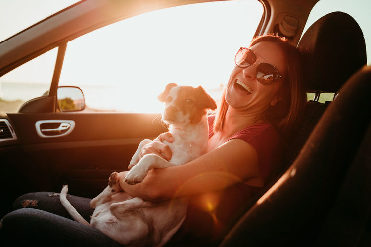 Portrait of smiling woman sitting in car with dog during sunset