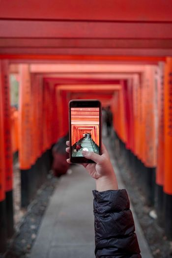 Cropped hand of person photographing shrine with mobile phone