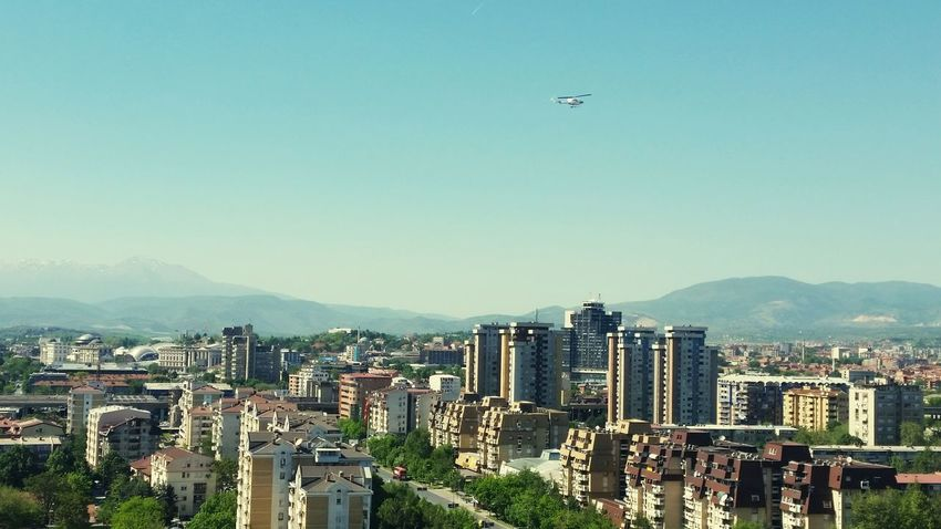 Mountain City Flying Outdoors Building Exterior Mountain Range Business Finance And Industry Helicopter EyeEmNewHere NewEyEm Cityscape Architecture Travel Destinations Urban Skyline Sky Day Capital City Skopje Macedonia GalaxyS5 The City Light