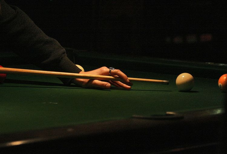 Cropped hands of man playing with snooker on table