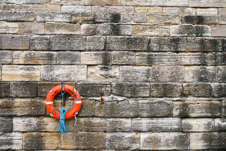 Life belt Life Saver Life Saving Equipment Life Saving Ring Safety First! Architecture Building Exterior Built Structure Day Hanging Life Belt No People Orange Color Outdoors Protection Red Safety Security Single Object Solid Stone Material Stone Wall Stone Wall Background Wall Wall - Building Feature