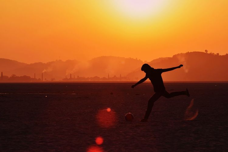 Silhouette Man Kicking Football Against Sky During Sunset