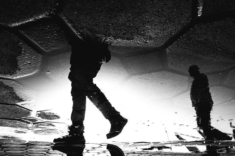 Low section of people walking on wet street