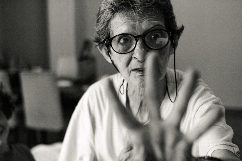 Portrait of woman wearing eyeglasses gesturing while sitting at home