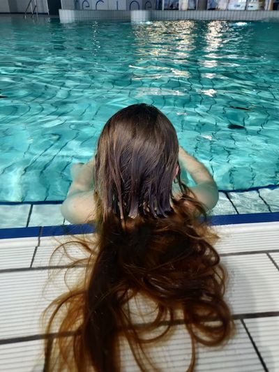 Rear view of woman with swimming pool