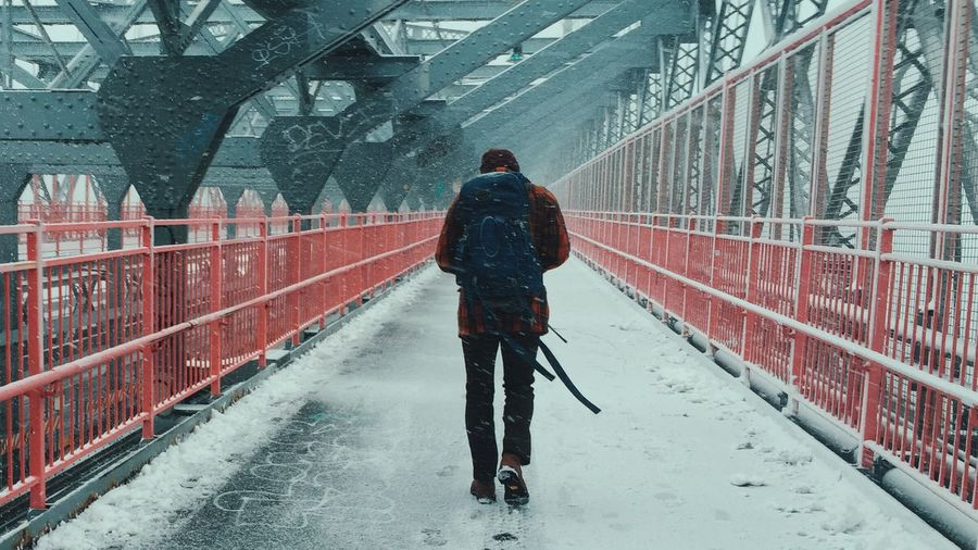 Full Length Rear View Of Man Walking On Bridge During Snowfall