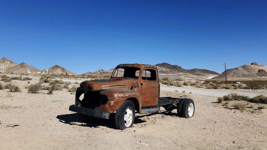 Abandoned Car On Desert Against Clear Sky