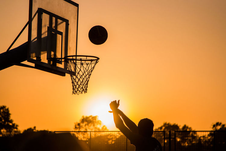 Silhouette Man Playing Basketball Against Sky During Sunset