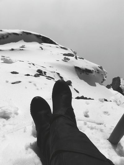 Low Section Of Person In Boots On Snow Covered Field Against Sky
