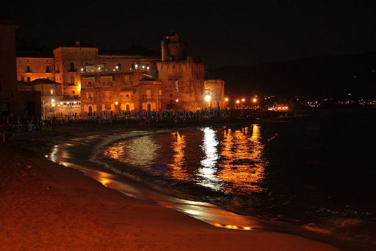 """Norman-Aragonese tower of the """"Pagliarola"""", Campania (Italy). 18-55mm Architecture Canon Canonphotography Castellabate Illuminated Lights Night Night Lights No People Nofilter Non-urban Scene Outdoors Reflected Light Reflection Reflections In The Water Riflessi Seafront Tower Water"""