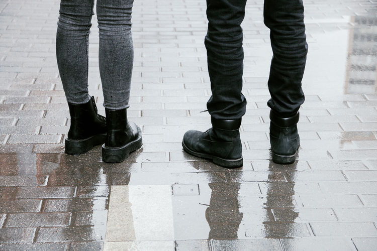Low section of people standing on wet footpath