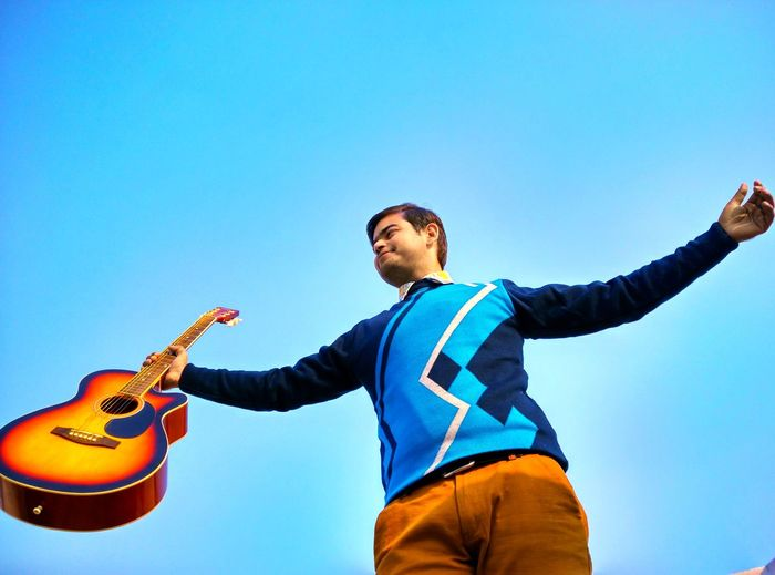 Low angle view of man holding guitar against clear blue sky