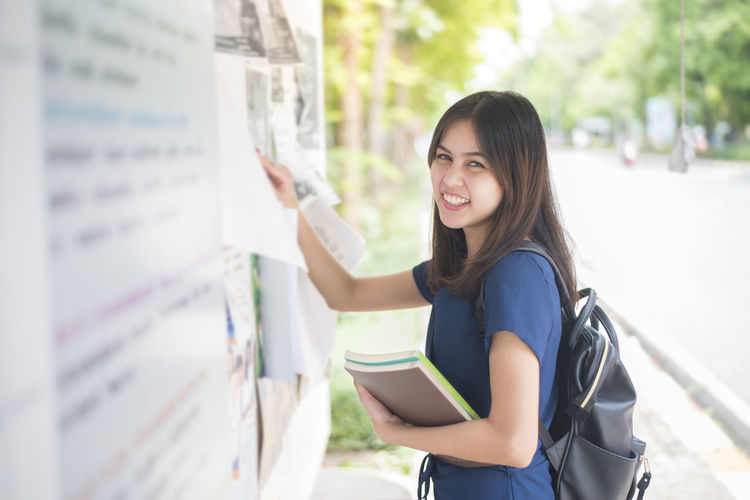 Portrait Of Smiling University Student Checking Test Result On Bulletin Board
