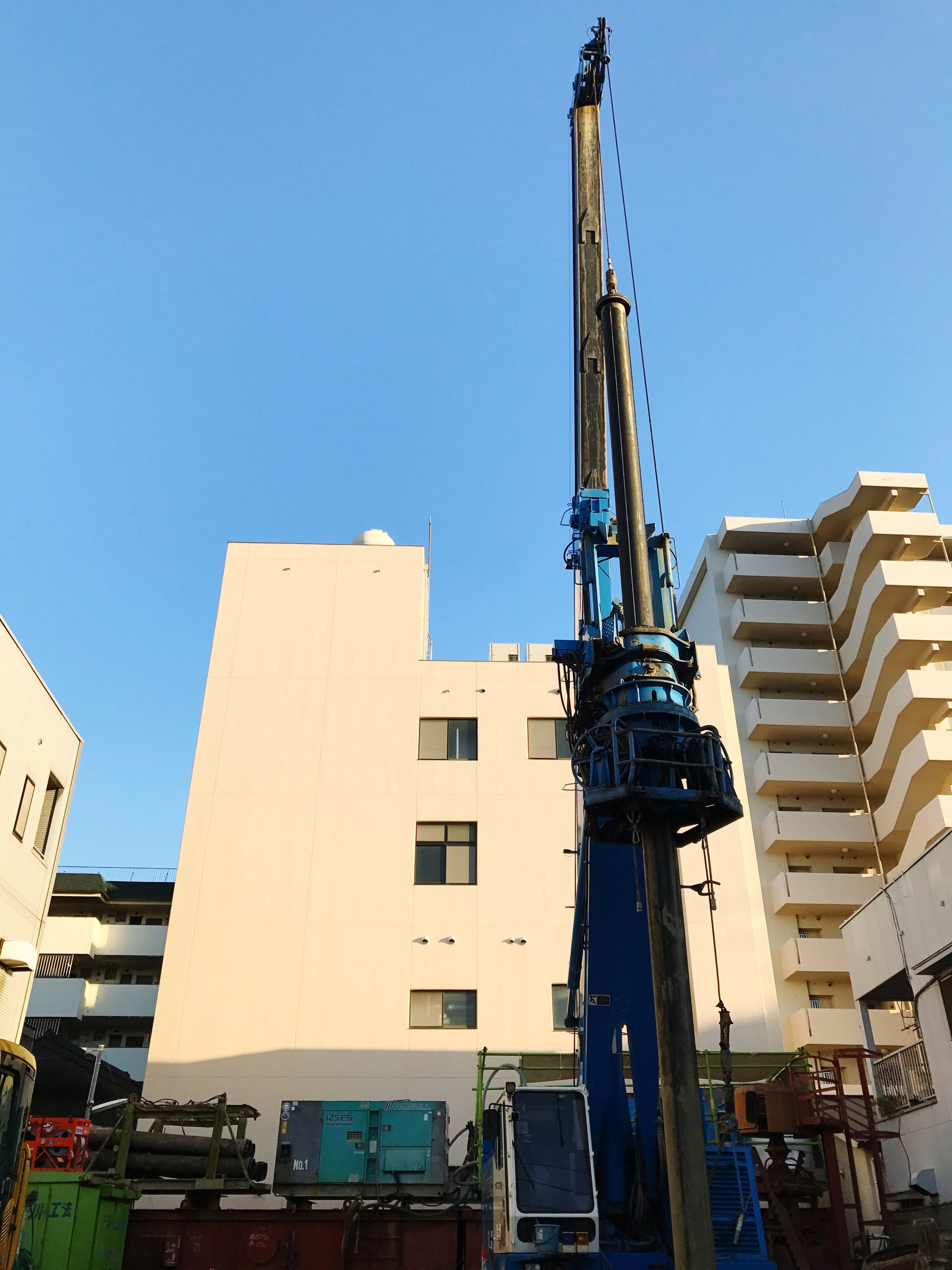 low angle view, architecture, clear sky, built structure, building exterior, crane - construction machinery, blue, outdoors, day, construction site, no people, sky