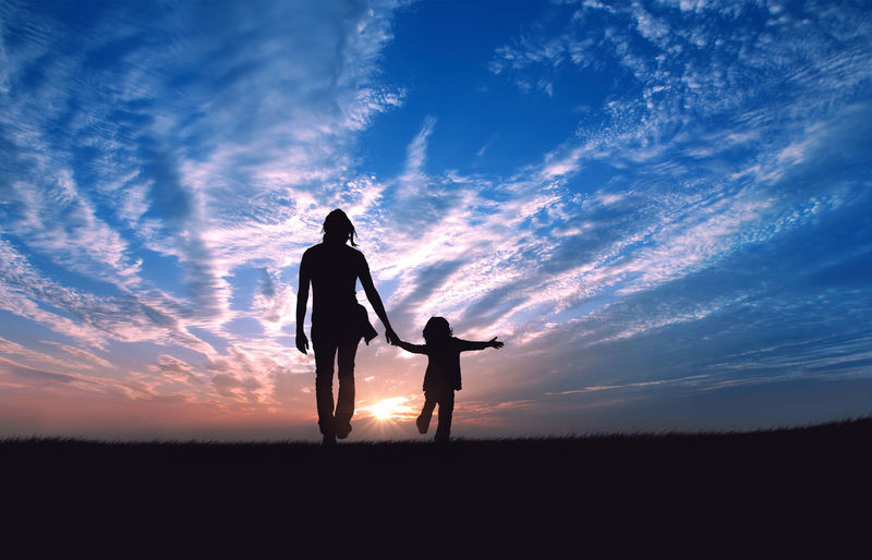 Silhouette of father and son standing on field at sunset