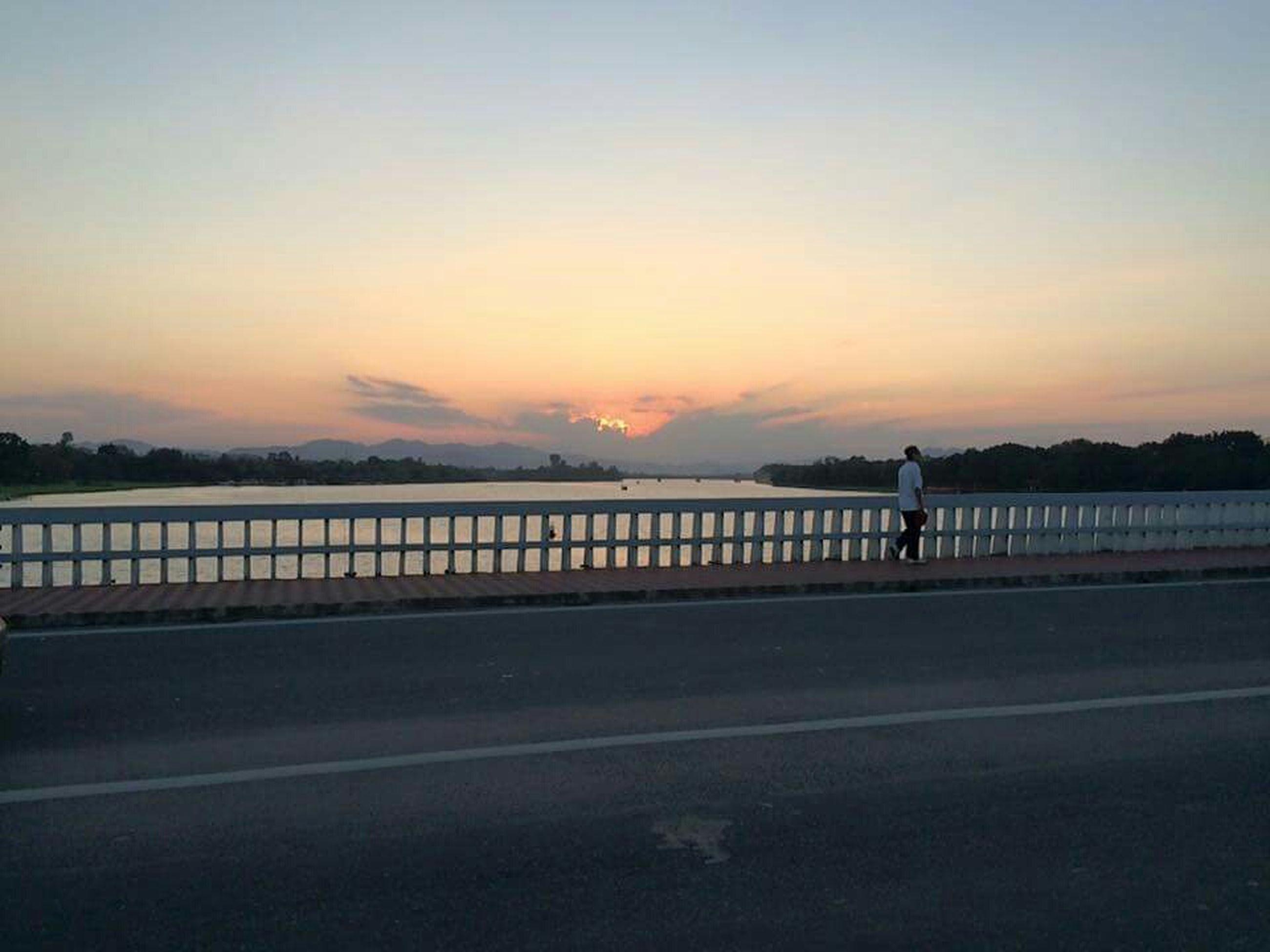 sunset, silhouette, lifestyles, men, leisure activity, sky, full length, road, walking, transportation, standing, rear view, orange color, dusk, street, nature, tranquil scene