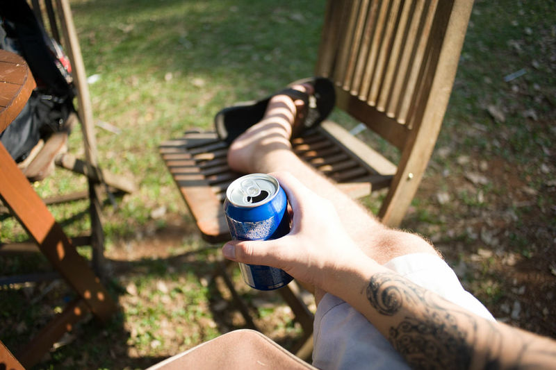 High angle view of man holding drink while sitting on chair