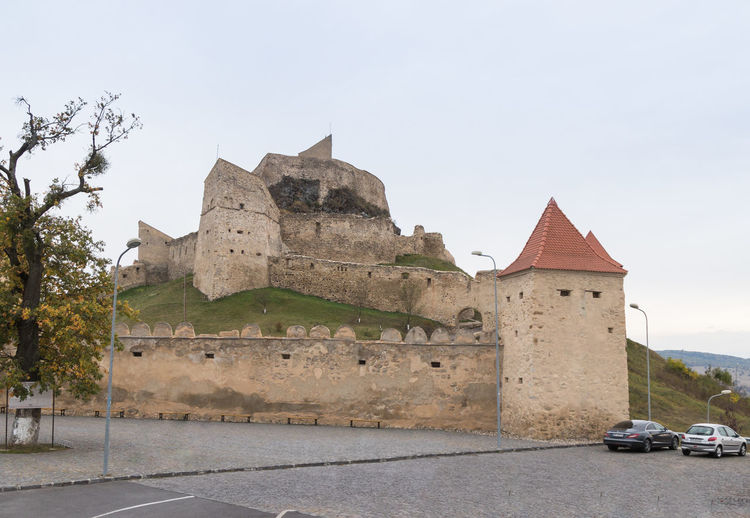 Near Sighisoara, Romania, October 08, 2017 : Fragment of the fortress wall of the Rupea Citadel built in the 14th century on the road between Sighisoara and Brasov in Romania Ancient Architecture Gothic Ruins Rupea Castle Sighisoara-Romania Transylvania Travel Brashov Citadel Day Destination Europe Fort Fortification Fortress Heritage History Medieval Monument Old Outdoors Tourism Tower Vacation