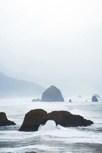 Rock formation in sea against sky during foggy weather