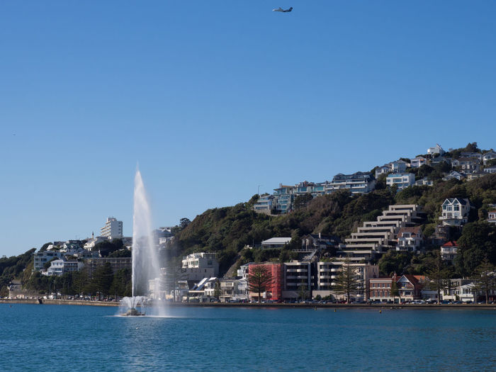 Fountain in the harbour City Clear Sky Fountain Harbour Harbour View Outdoors Plane Flying Plane Flying Past Urban Skyline Water Fountain
