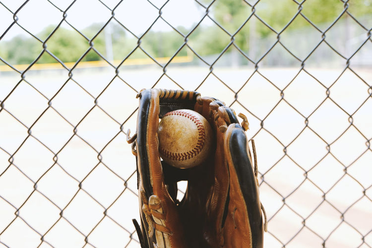 Baseball in glove behind chainlink fence for protection. Ball Barrier Baseball - Ball Baseball - Sport Baseball Glove Boundary Chainlink Fence Close-up Day Fence Focus On Foreground Glove Metal No People Outdoors Protection Safety Security Sport