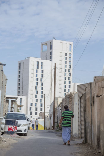 Rear view of man walking on city street against sky