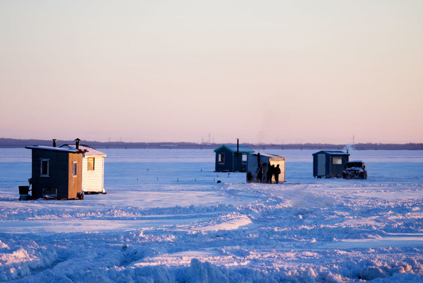 Ice fishing huts and a car on a frozen lake. One of the hut has smoke coming out of the chimney. Beauty In Nature Building Exterior Built Structure Cold Temperature Day Frozen Ice Fishing Huts Ice Fishing Huts On Frozen Lake At Sunset Ice Fishing Shack Landscape Nature No People Outdoors Scenics Sea Sky Snow Snowdrift Sunset Winter
