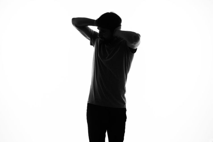 Rear view of young man against white background