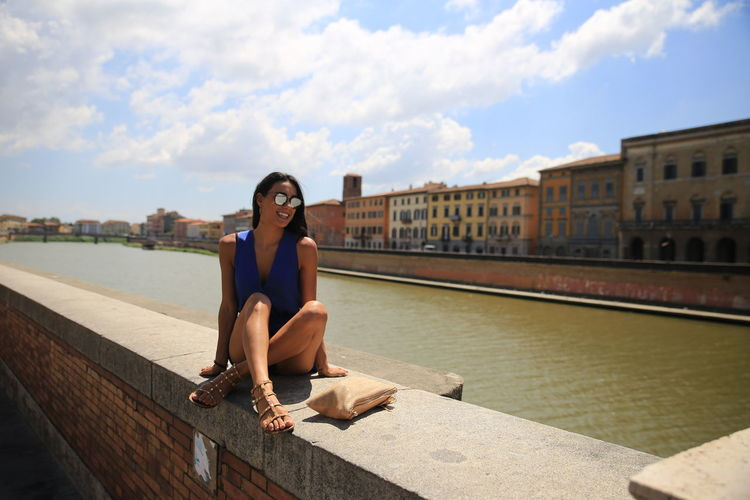 Full Length Of Smiling Young Woman Wearing Sunglasses While Sitting On Retaining Wall Against Sky In City