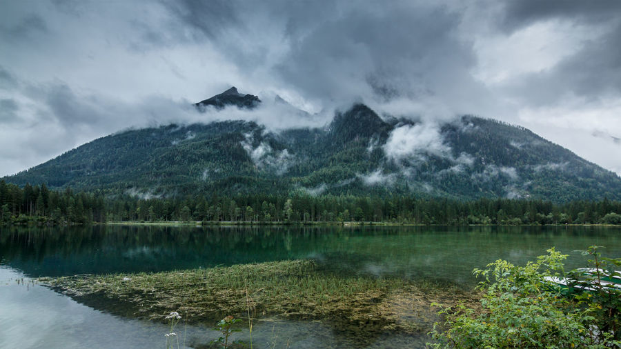 Scenic view of hintersee lake by mountain against cloudy sky