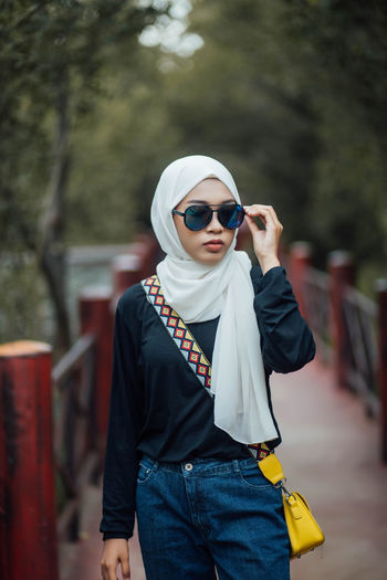 Young woman wearing sunglasses while standing on footpath