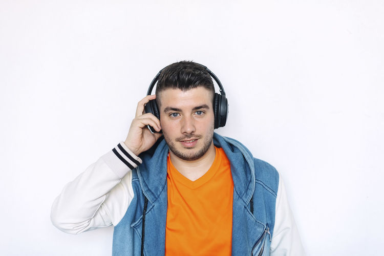 Male Happiness Enjoy Adult Play Joy Holding Headphone Dance Radio Hear Lifestyle Music Modern Attractive Isolated Human Smile Hair Sound Hand Song Background Sing Man Entertainment Young person Casual Listen Happy Handsome Audio Portrait Studio Mp3 Cool Relax Student Technology Hispanic White Face Party Youth Earphones Disco One Person Front View Clothing Indoors  Young Adult Young Men