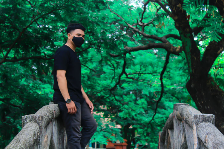 Young man wearing mask standing against tree