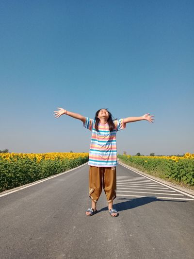 Full length girl with arms outstretched standing on road