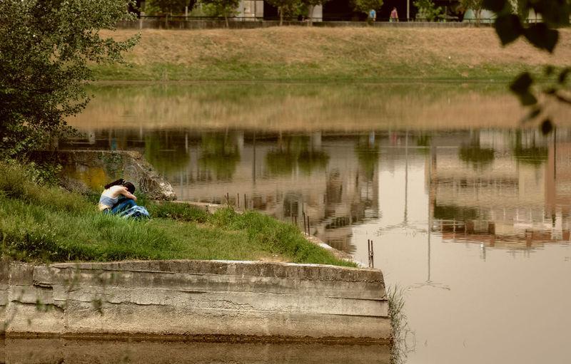 Rear view of man sitting by lake