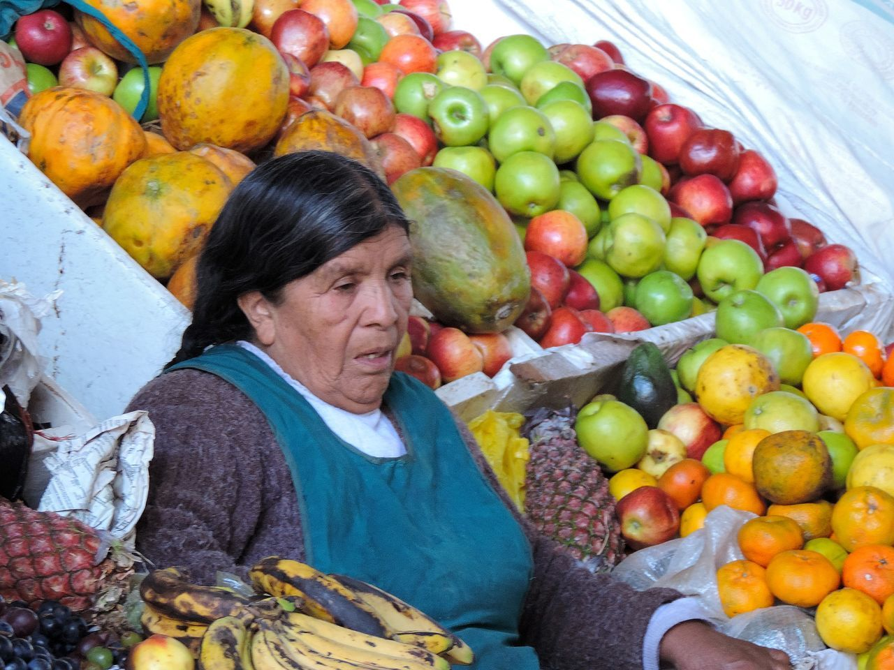 fruit, orange - fruit, food, healthy eating, food and drink, apple - fruit, choice, mature adult, freshness, senior adult, large group of objects, outdoors, basket, abundance, grape, one person, day, women, market, peach, looking at camera, only women, portrait, adults only, adult, grapefruit, pomegranate, one woman only, people