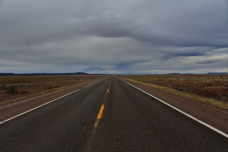 Empty Road Passing Through Landscape Against Cloudy Sky