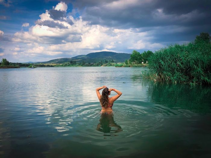Woman in the water surrounded by green vegetation and dark storm clouds