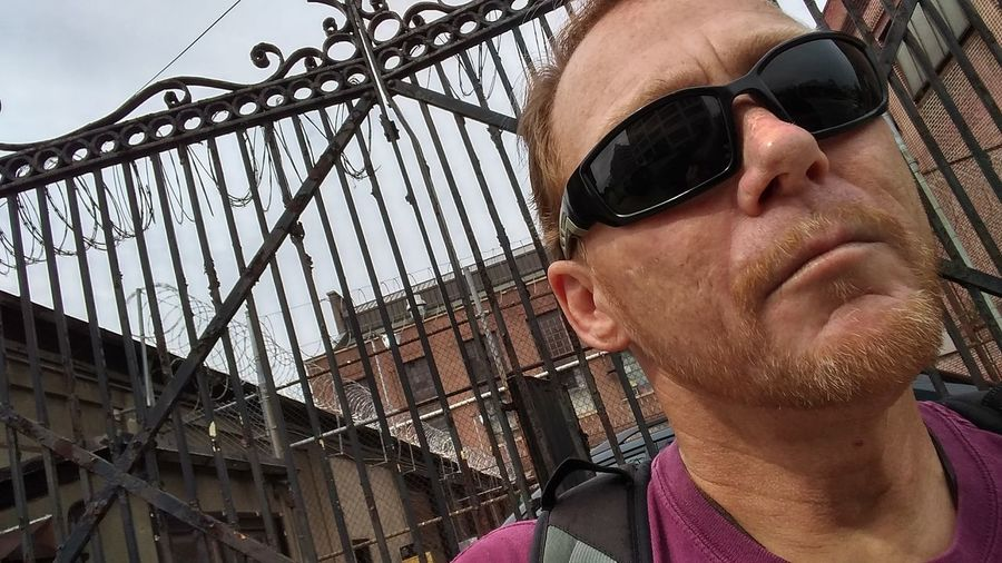 Close-up of mature man wearing sunglasses against closed gate