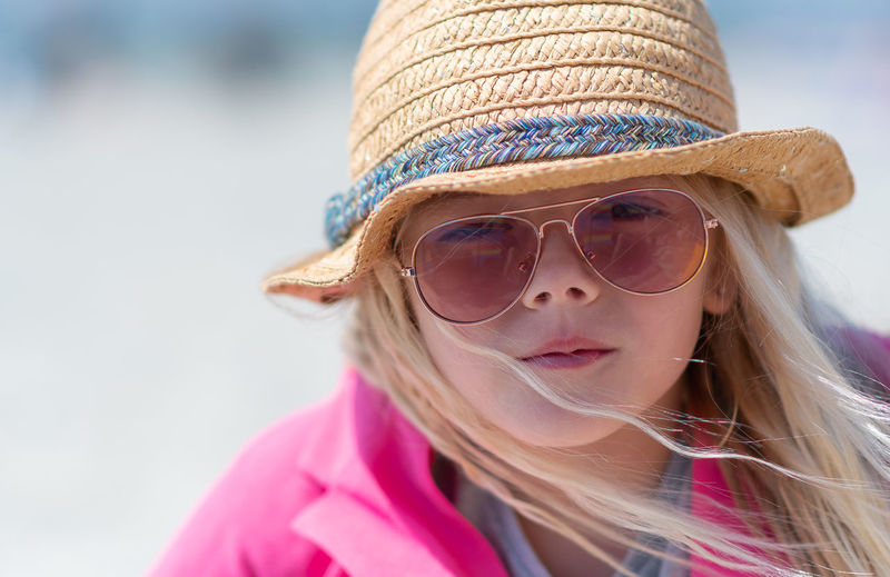 Close-Up Portrait Of Girl Wearing Hat And Sunglasses At Beach During Summer