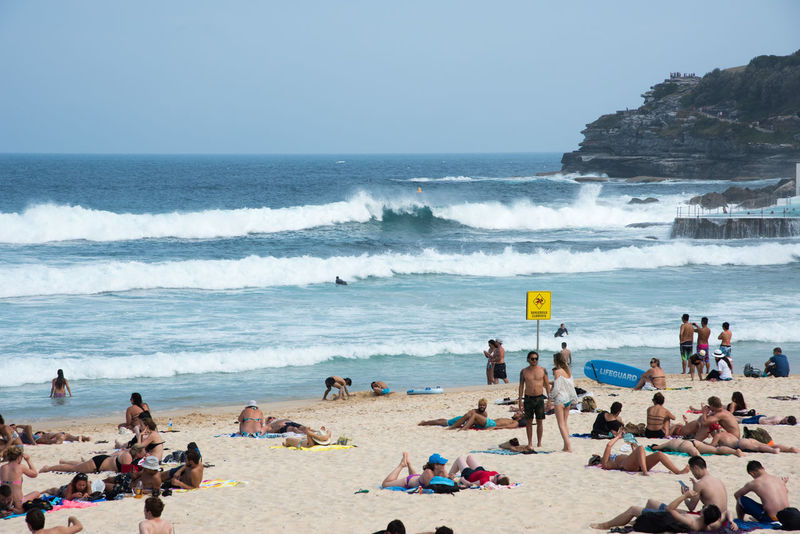 SYDNEY,NSW,AUSTRALIA-NOVEMBER 21,2016: Crowds at Bondi Beach with turquoise Pacific Ocean waters in Sydney, Australia. Australia Beach Bondi Crowd Current Dangerous Enjoyment Leisure Activity Lifeguard  Mixed Age Range Nature Pacific Ocean Powerful Real People Sand Scenics Sea Summer Sunbathing Surfboard Sydney Travel Destinations Vacations Water Wave