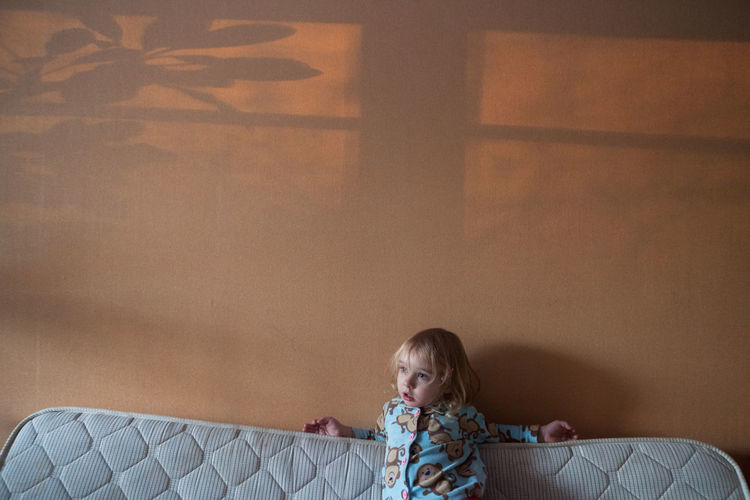 Girl against wall on sofa in living room at home