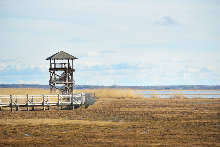 Lifeguard tower on field against sky