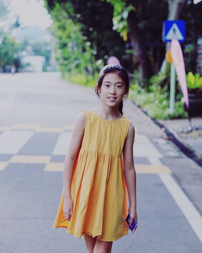 Portrait Of Smiling Girl Walking On Road