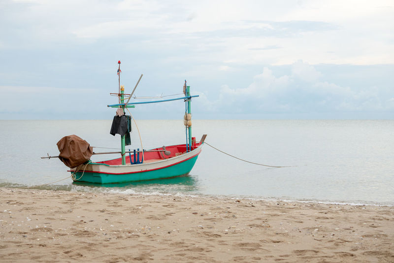 Small traditional fishing boat floating in the sea at coast with calm surface of ocean and clouded sky Water Sea Sky Nautical Vessel Transportation Mode Of Transportation Beach Cloud - Sky Land Nature Day Horizon Beauty In Nature Scenics - Nature Horizon Over Water Sand Outdoors Travel Destinations Transportation Occupation Job Fising Cultures Traditional