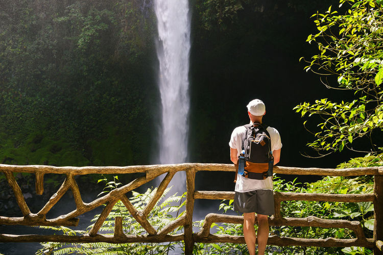 Man standing by waterfall against trees