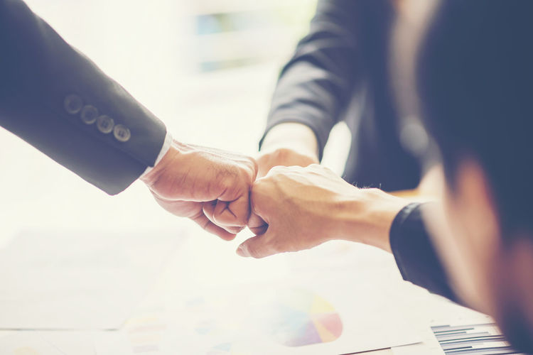 Cropped hands of business colleagues doing fist bump in office